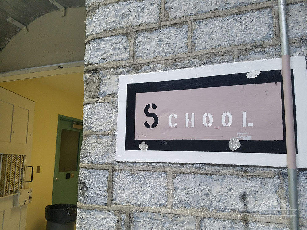 School sign on stone wall in the workshop building